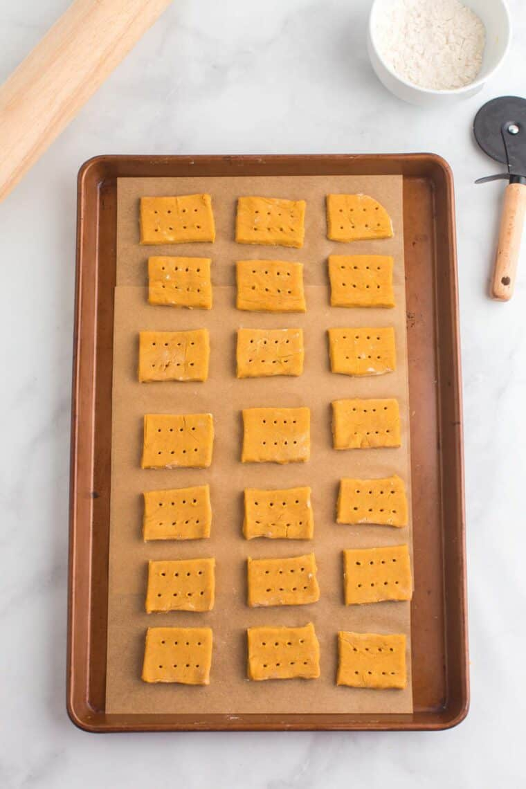 unbaked pumpkin cookies on a parchment-lined sheet pan