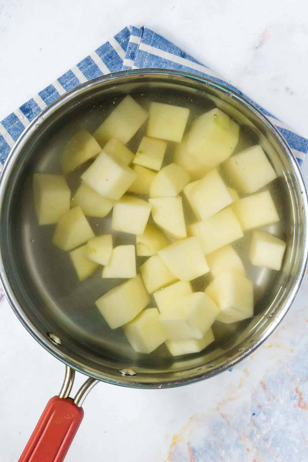 cubed potatoes in a small pot of water