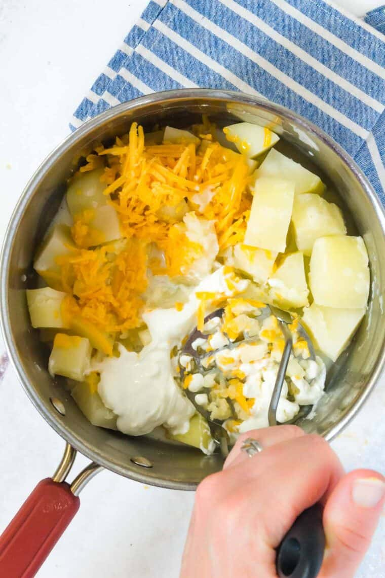 using a hand masher to mash boiled potatoes with milk, greek yogurt, and cheddar cheese