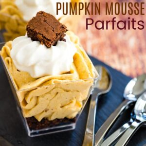 pumpkin mousse parfait with a brownie base on a slate platter with mini spoons